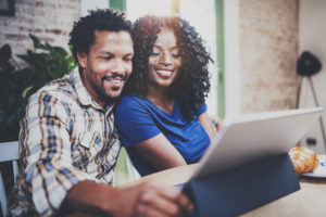 Smiling young african american couple having online conversation together via touch tablet at the morning in living room.Blurred background.Flare.